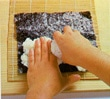 Adding the sushi rice to the nori